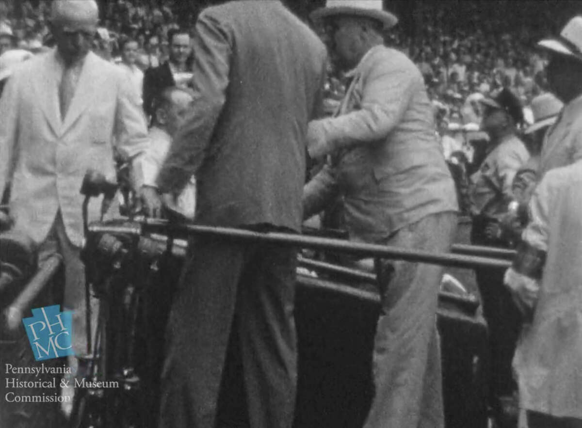 In this image taken from film shot by former Major League Baseball player Jimmie DeShong and acquired by the Pennsylvania Historical & Museum Commission, President Franklin D. Roosevelt, center right, walks to his seat with the aid of an assistant at the Major League Baseball All-Star game on July 7, 1937 at Griffith Stadium in Washington. The rare footage helps dispel the myth that he tried to hide his disability and shows the courage it took to go about his daily life, experts said Friday, May 16, 2014. (AP Photo/Pennsylvania Historical & Museum Commission) ORG XMIT: NY112