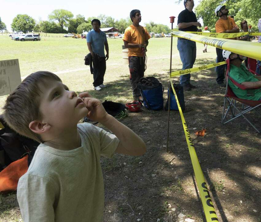 Topher Nelson, 6, watches as climbers compete in the Texas Tree Climbing Championship in New Braunfels. Events include the throw line, foot lock, aerial rescue and work climb.