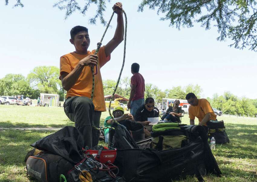 Miguel Pastenes, a six-time state champ known for his speed, organizes his equipment during the tree-climbing competition.