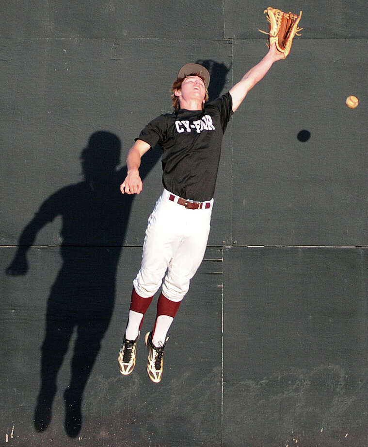 Cy-Fair left fielder Maxx Chrest playfully misses a fly ball during batting practice before a high school baseball playoff game against Cy-Ranch, Friday, May 16, 2014, at Cy-Woods High School in Cypress. Photo: Eric Christian Smith, For The Chronicle