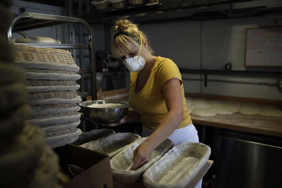 Baker Crystal White sprinkles flour into baskets that bread will be baked in at Tartine Bakery. Photo: Michael Short, The Chronicle