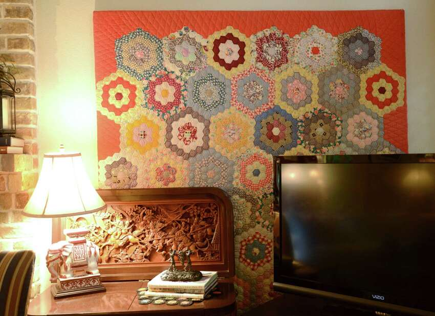 An antique quilt bought at an estate sale adorns a living room wall in the home of Susan and Stan Marett.