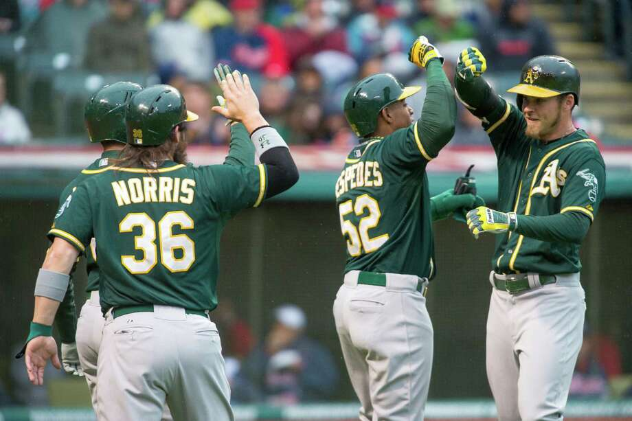 The Athletics' Josh Reddick, right, is congratulated by Yoenis Cespedes after hitting a grand slam in the second inning of Friday's win over the Indians. Photo: Jason Miller, Stringer / 2014 Getty Images