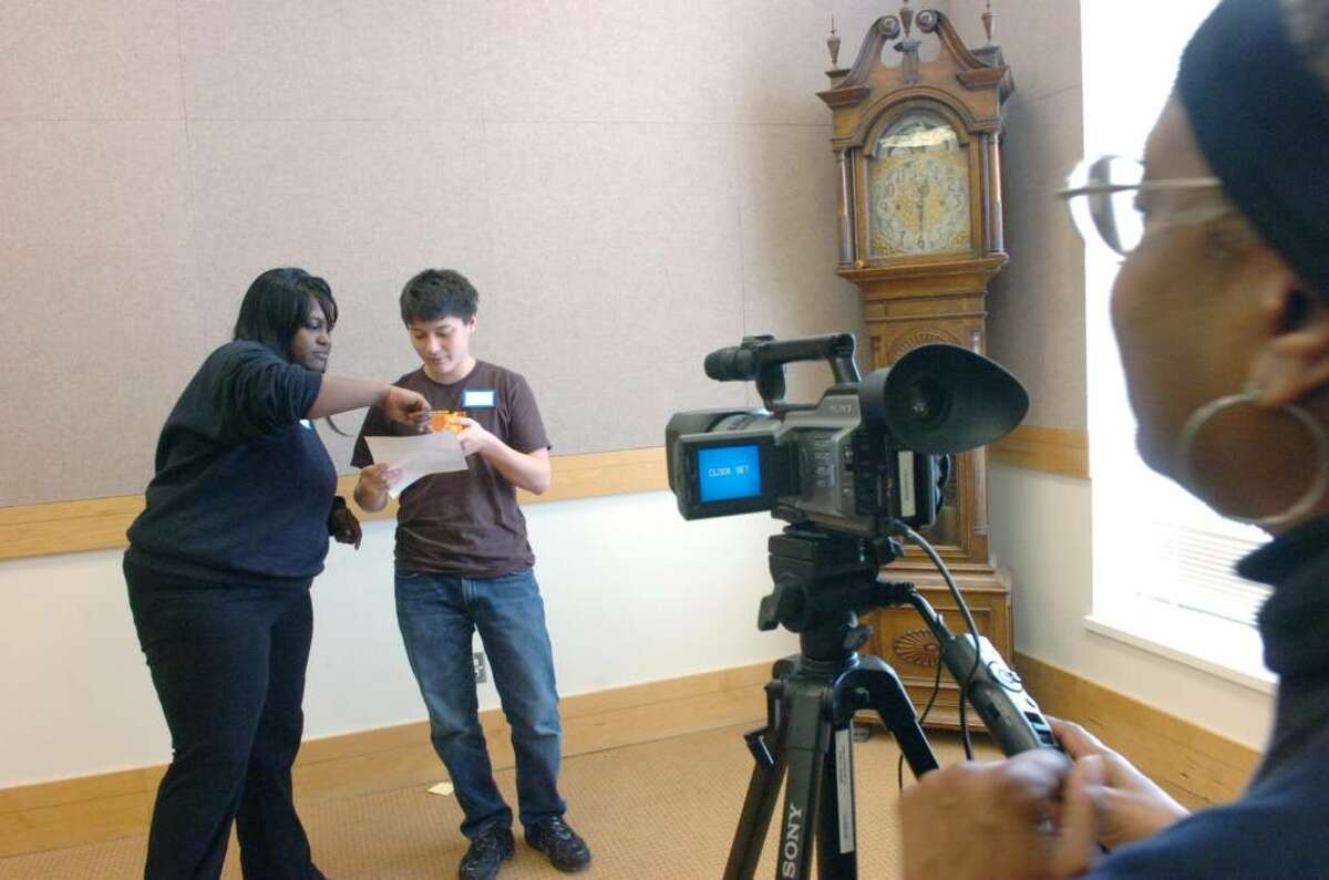 Leslie Addy preps Josh Goroff, 15, for a reading as Addy's mom and director Vicki Camacho prepares to tape the audition for a musical about the game of chess Saturday, February 13, 2010 at Greenwich Library's meeting room. Camacho wrote a short musical which features the