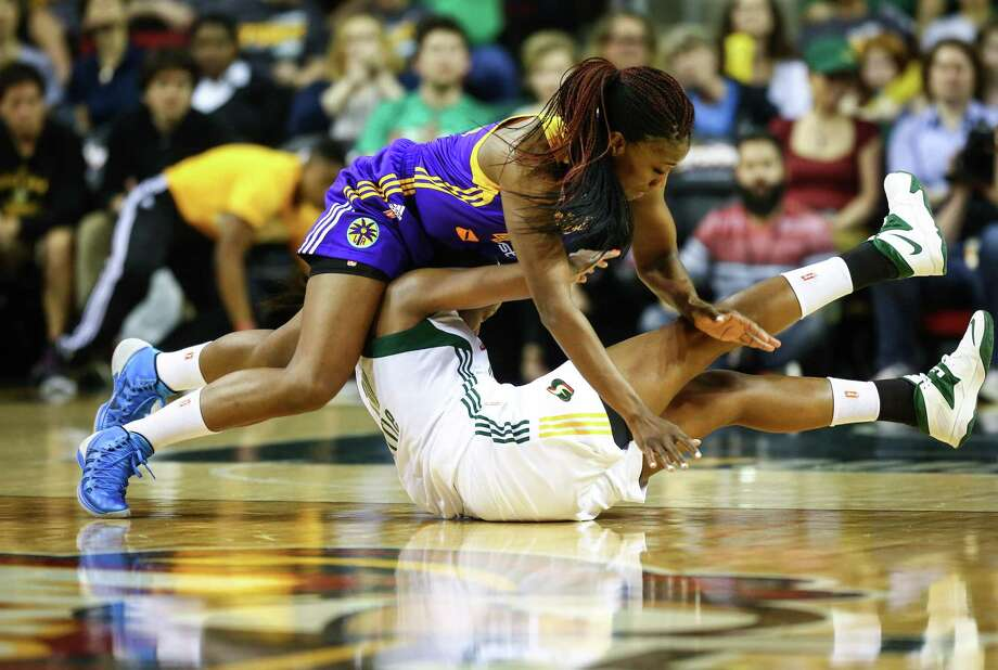 Sparks player Jantel Lavender falls on Storm player Camille Little during the Seattle Storm season opener on Friday, May 16, 2014 at KeyArena in Seattle. Photo: JOSHUA TRUJILLO, SEATTLEPI.COM / SEATTLEPI.COM
