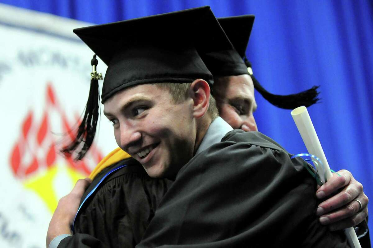 Graduate Jason Roth left, embraces his father, faculty member Gregg Roth, who delivers the diploma during commencement exercises on Friday, May 16, 2014, at Fulton-Montgomery Community College in Johnstown, N.Y. (Cindy Schultz / Times Union)