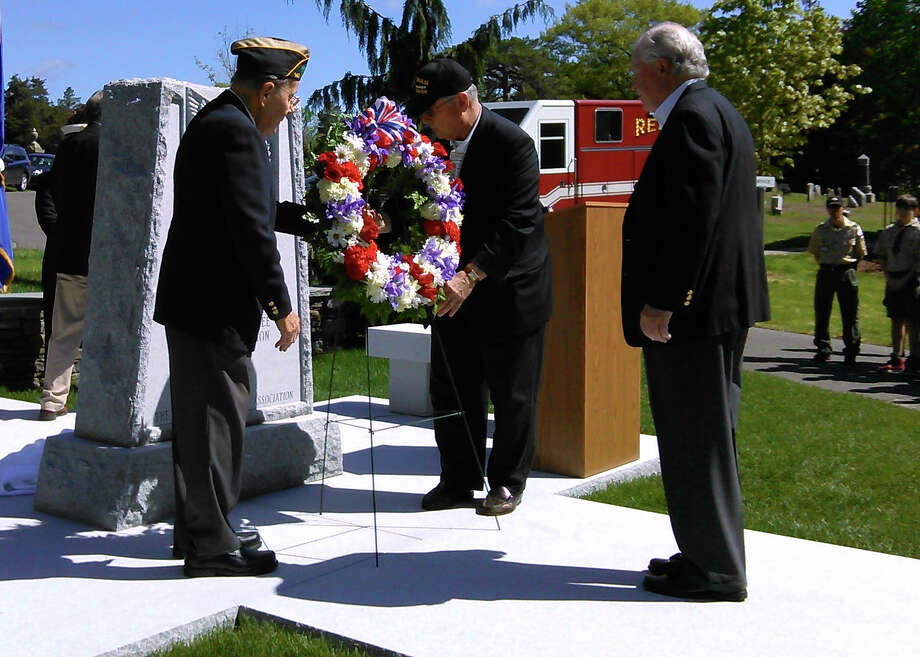 First Selectman Michael Tetreau, right, prepares to lay a wreath at Oak Lawn Cemetery's new memorial to military veterans during a dedication service Saturday. Photo: Andrew Brophy / Fairfield Citizen