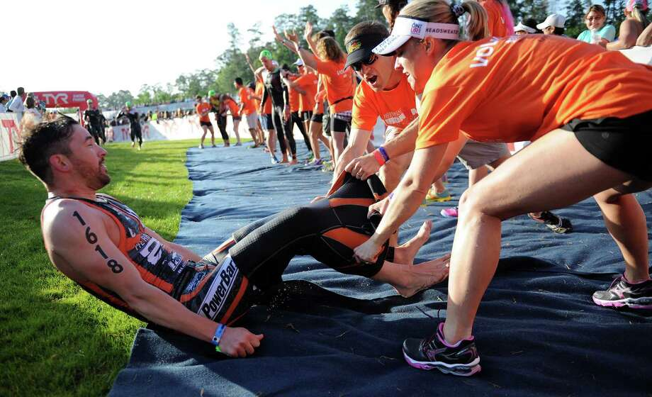Volunteers help take off the wetsuit of during the Ironman Texas triathlon, Saturday, May 17, 2014, in The Woodlands. Photo: Eric Christian Smith, For The Chronicle