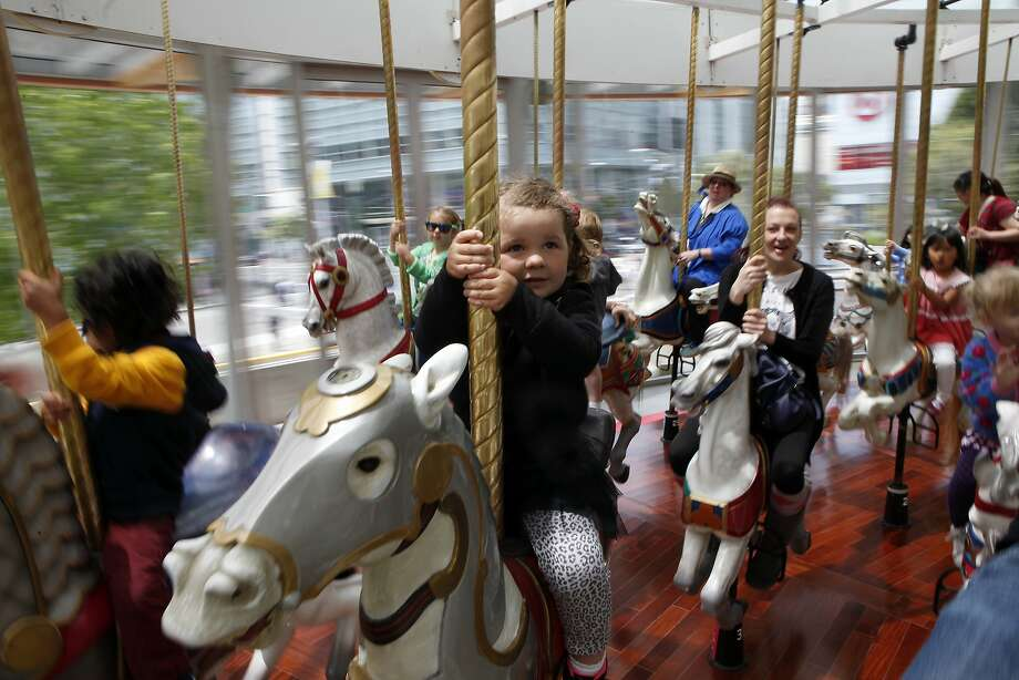 Julia Yudskya, 2, of Pleasant Hill holds on as she rides the newly restored LeRoy King Carousel during the grand reopening ceremony at Yerba Buena Gardens in San Francisco, CA, Saturday May 17, 2014. Photo: Michael Short, The Chronicle