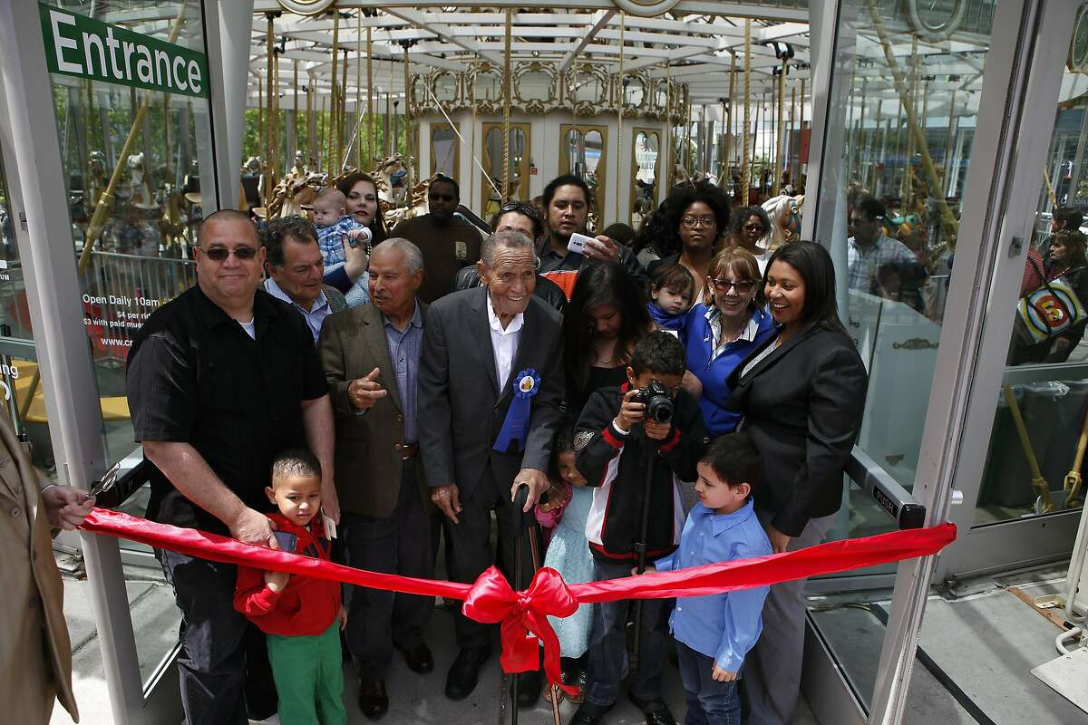 Former Commissioner of the San Francisco Redevelopment Agency, LeRoy King, center, is surrounded by family and friends for the ribbon cutting at the grand reopening ceremony for the LeRoy King Carousel at Yerba Buena Gardens in San Francisco, CA, Saturday May 17, 2014.