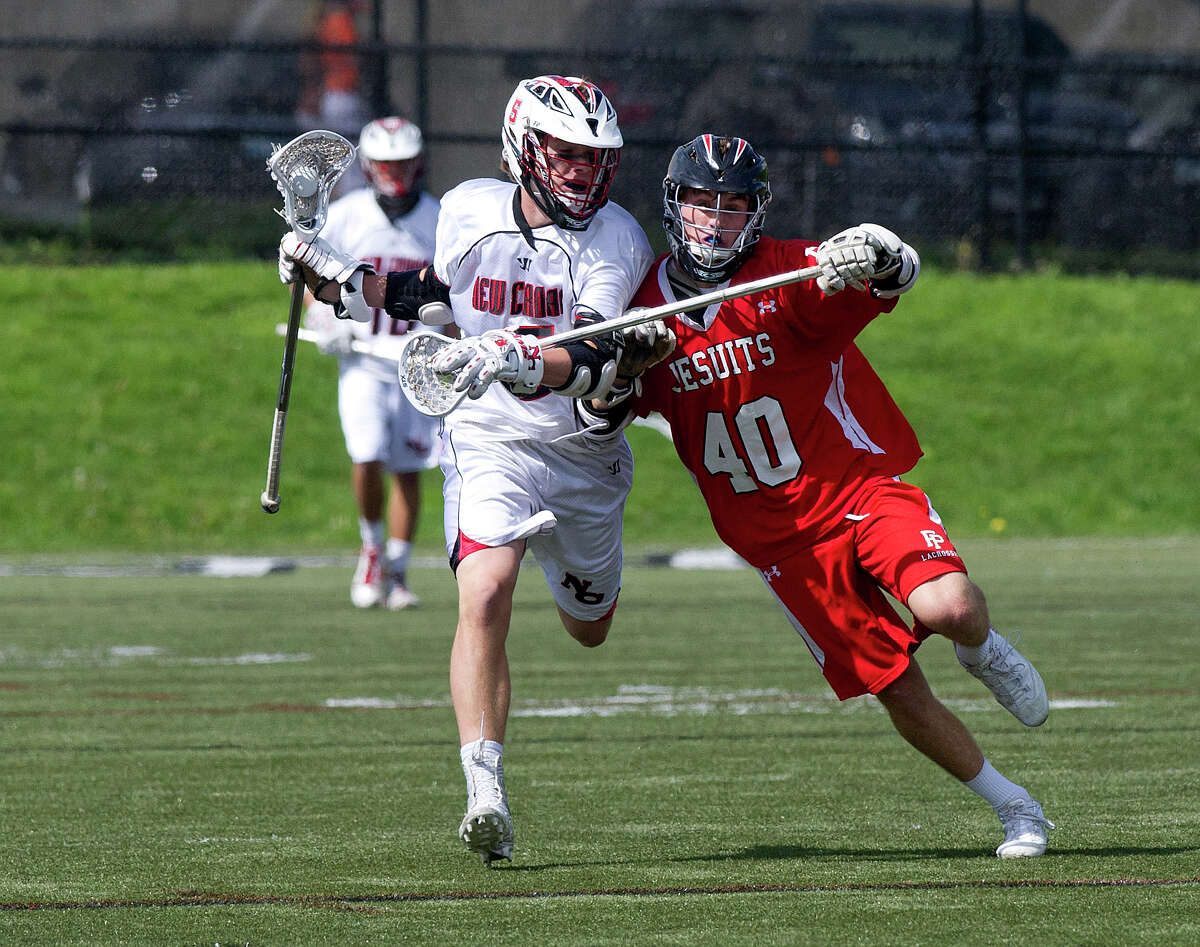 New Canaan's Graham Wagner controls the ball as he is defended by Fairfield Prep's Patrick Lambert during Saturday's lacrosse game at New Canaan High School on May 17, 2014.