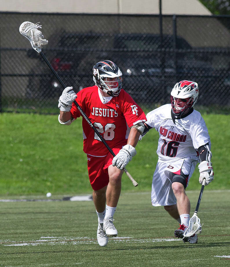 Fairfield Prep's Maxwell Trudeau carries the ball as he is defended by New Canaan's Harry Stanton during Saturday's lacrosse game at New Canaan High School on May 17, 2014. Photo: Lindsay Perry / Stamford Advocate