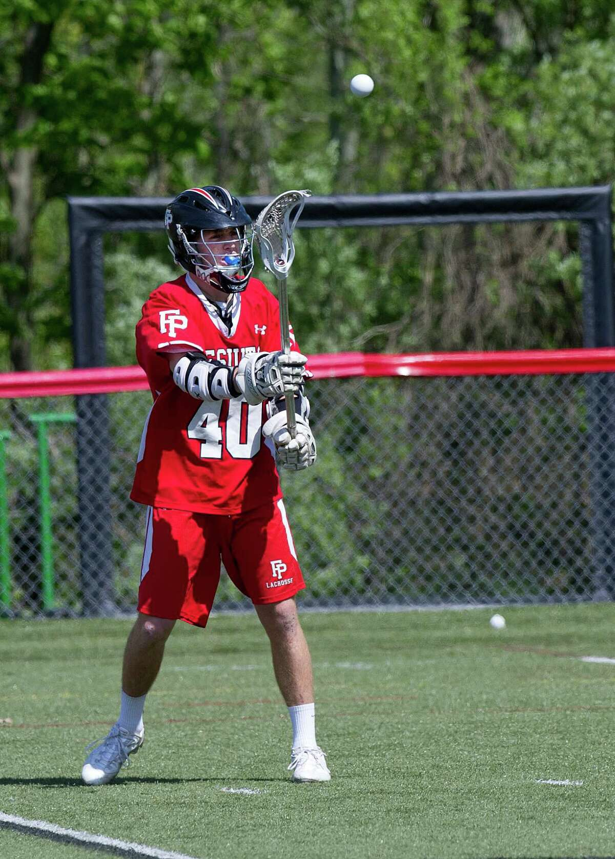 Fairfield Prep's Patrick Lambert passes the ball during Saturday's lacrosse game at New Canaan High School on May 17, 2014.