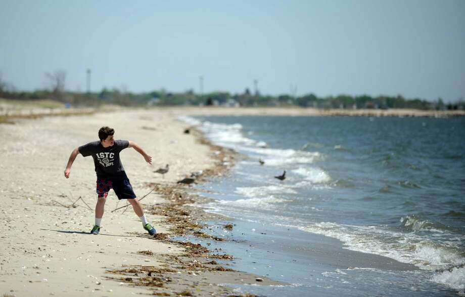 Volunteer Brian Tormey, 15, of Fairfield, stops to toss a shell into the Long Island Sound during a clean up of the Pleasure Beach Peninsula Saturday, May 17, 2014, in Bridgeport, Conn. The city plans to re-open the long-closed beach to the public this summer, making it accessible via water taxis. Photo: Autumn Driscoll / Connecticut Post
