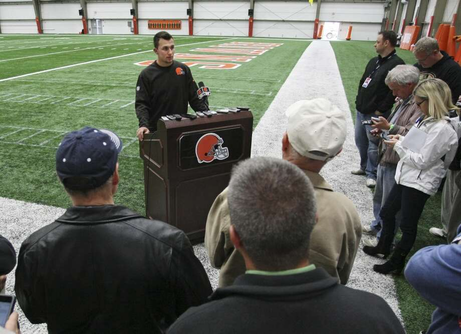 In this pool photo provided by the Cleveland Browns, quarterback Johnny Manziel talks with reporters after a workout at NFL football rookie minicamp at the team's facility in Berea, Ohio Saturday, May 17, 2014. (AP Photo/Cleveland Browns, John Reid, Pool) Photo: John Reid, Associated Press