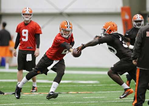 Cleveland Browns quarterback Johnny Manziel hands off during a rookie minicamp practice at the NFL football team's facility in Berea, Ohio Saturday, May 17, 2014. (AP Photo/Mark Duncan) Photo: Mark Duncan, Associated Press