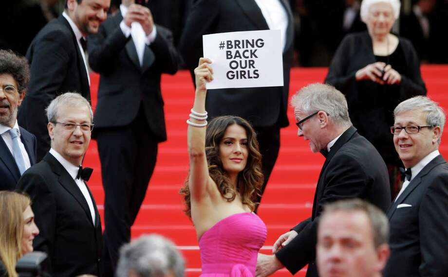 "Actress Salma Hayek holds up a sign reading ""bring back our girls"", part of a campaign calling for the release of nearly 300 abducted Nigerian schoolgirls being held by Nigerian Islamic extremist group Boko Haram, as she arrives for the screening of Saint-Laurent at the 67th international film festival, Cannes, southern France, Saturday, May 17, 2014. Photo: Thibault Camus, AP / THE ASSOCIATED PRESS2014"