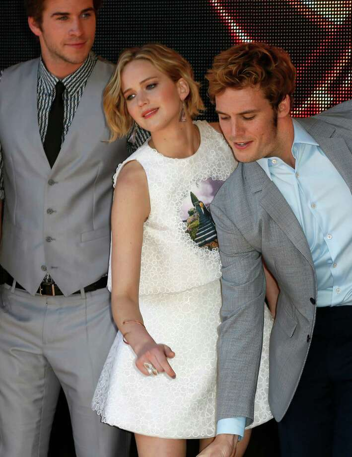 From left, actors Liam Hemsworth, Jennifer Lawrence and Josh Hutcherson pose for photographers during a photo call for Hunger Games: Mockingjay Part 1 at the 67th international film festival, Cannes, southern France, Saturday, May 17, 2014. Photo: Alastair Grant, AP / AP