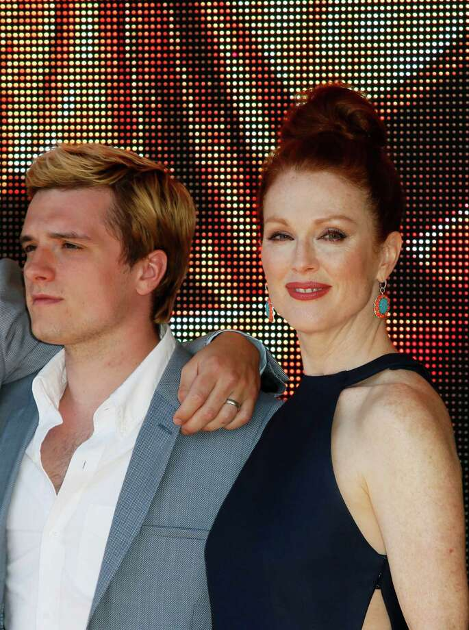 From left, actors Josh Hutcherson and Julianne Moore pose for photographers during a photo call for Hunger Games: Mockingjay Part 1 at the 67th international film festival, Cannes, southern France, Saturday, May 17, 2014. Photo: Alastair Grant, AP / AP2014