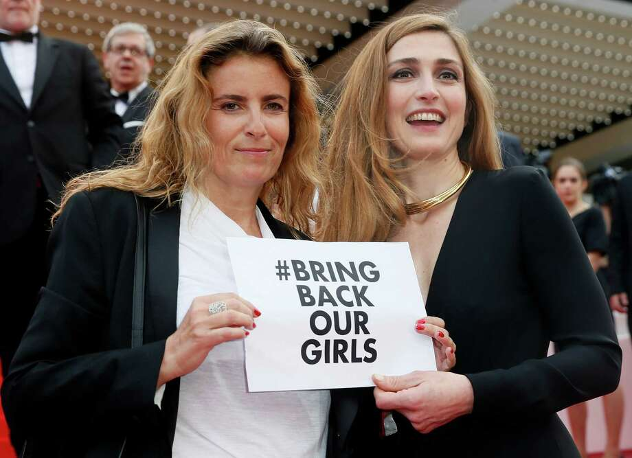 "Actress Julie Gayet, right, and director Lisa Azuelos hold a sign reading ""bring back our girls"", part of a campaign calling for the release of nearly 300 abducted Nigerian schoolgirls being held by Nigerian Islamic extremist group Boko Haram, as they arrive for the screening of Saint-Laurent at the 67th international film festival, Cannes, southern France, Saturday, May 17, 2014. Photo: Alastair Grant, AP / AP"