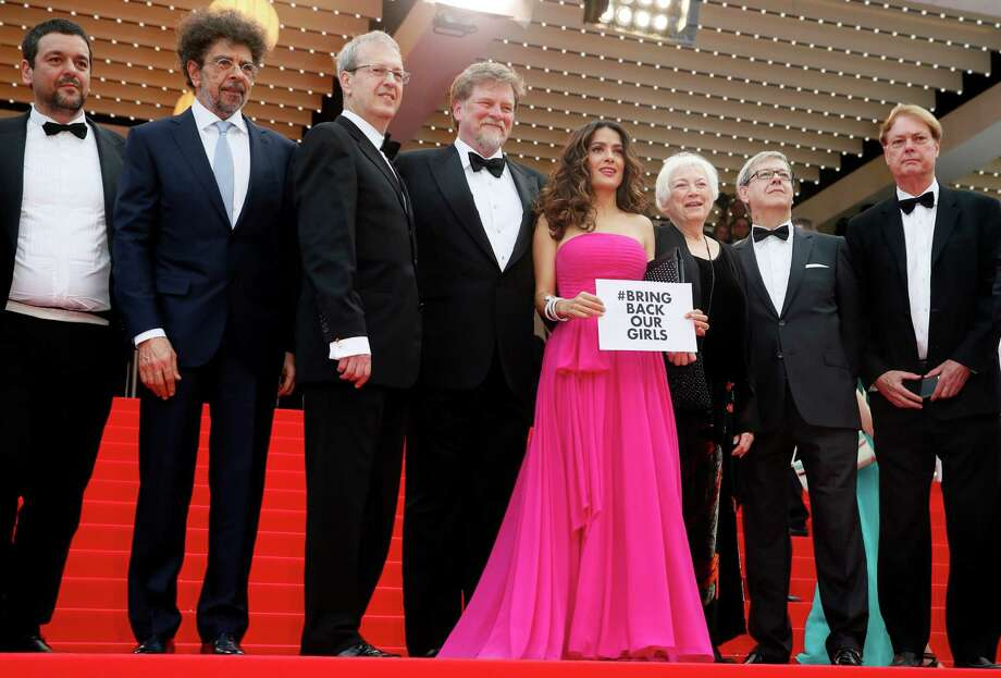 Actress Selma Hayek-Pinault, fourth right, holds up a sign as she arrives for the screening of Saint-Laurent at the 67th international film festival, Cannes, southern France, Saturday, May 17, 2014. Photo: Alastair Grant, AP / AP