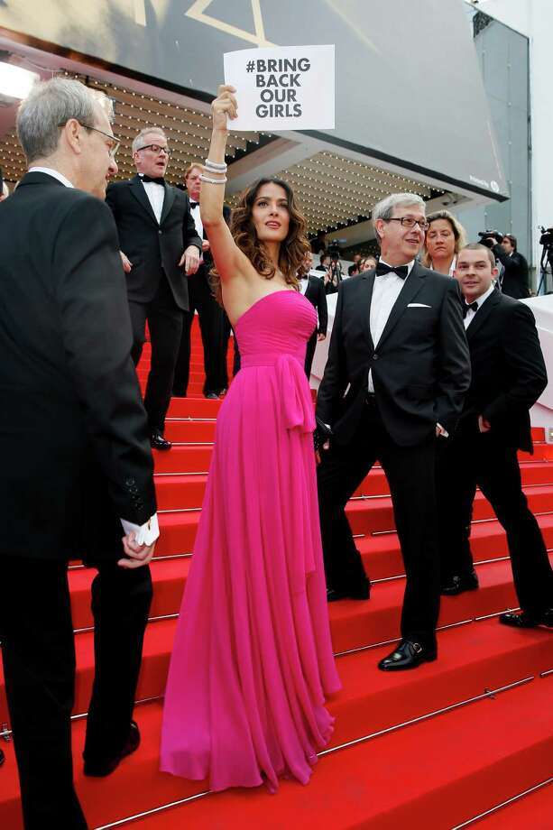 """Actress Salma Hayek holds up a sign reading """"bring back our girls"""", part of a campaign calling for the release of nearly 300 abducted Nigerian schoolgirls being held by Nigerian Islamic extremist group Boko Haram, as she arrives for the screening of Saint-Laurent at the 67th international film festival, Cannes, southern France, Saturday, May 17, 2014. Photo: Alastair Grant, AP / AP"""