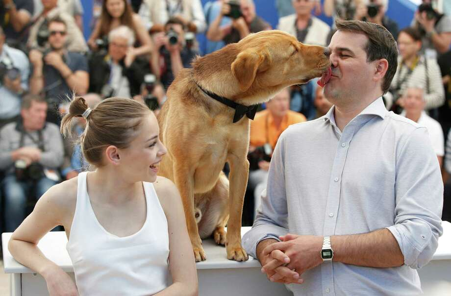 Actress Zsofia Psotta, left, looks on as director Kornel Mundruczo is licked in the face by a dog during a photo call for White God (Feher Isten) at the 67th international film festival, Cannes, southern France, Saturday, May 17, 2014. Photo: Alastair Grant, AP / AP2014