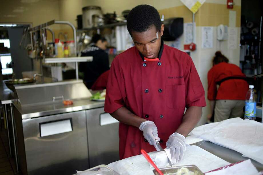 Kevin Victor, 18, prepares a wrap at a cafe in Children's Village in Dobbs Ferry, N.Y., where he lives in a cottage and participates in the culinary arts program. Photo: Seth Wenig, STF / AP