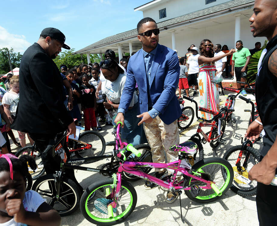 Earl Thomas III picks out the next bicycle to be given away to a child during Saturday morning's event. Sixty bicycles were given to children by the Earl Thomas III Guardian Angel Foundation at Sixth Street Community Church in Orange on Saturday morning.