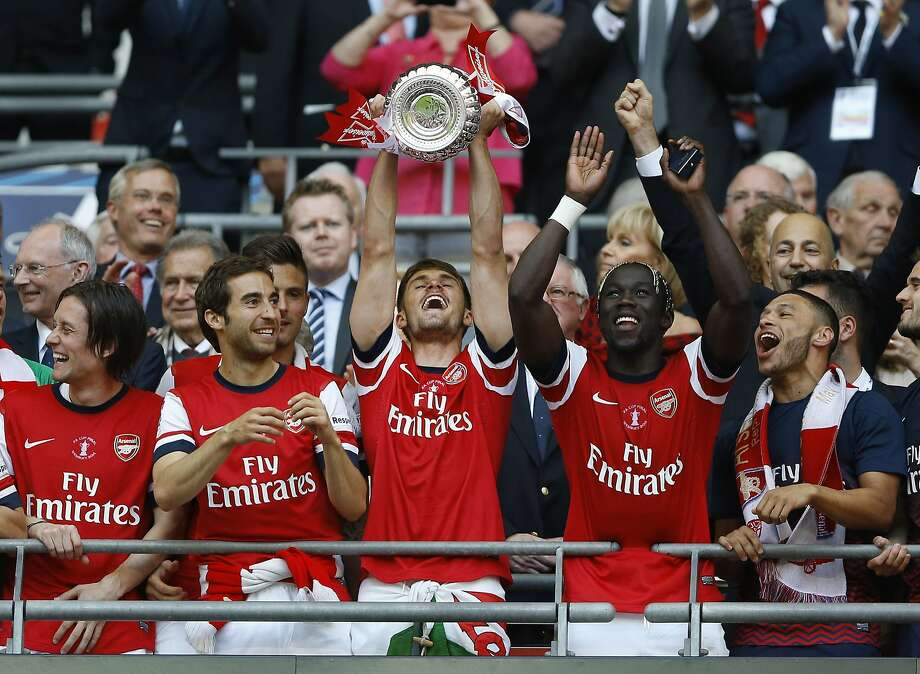 Arsenal's Aaron Ramsey holds the trophy aloft as he celebrates after his team won the English FA Cup final soccer match between Arsenal and Hull City at Wembley Stadium in London, Saturday, May 17, 2014. Arsenal won 3-2 after extra-time. (AP Photo/Kirsty Wigglesworth) Photo: Kirsty Wigglesworth, Associated Press