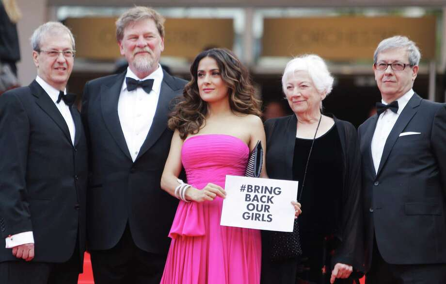 "Actress Salma Hayek, center, holds up a sign reading ""bring back our girls"", part of a campaign calling for the release of nearly 300 abducted Nigerian schoolgirls being held by Nigerian Islamic extremist group Boko Haram, as she arrives for the screening of Saint-Laurent at the 67th international film festival, Cannes, southern France, Saturday, May 17, 2014. At left is director Paul Brizzi, second left, director Roger Allers, second right director Joan C. Gratz and director Gaetan Brizzi. (AP Photo/Thibault Camus) ORG XMIT: CAN196 Photo: Thibault Camus / AP"