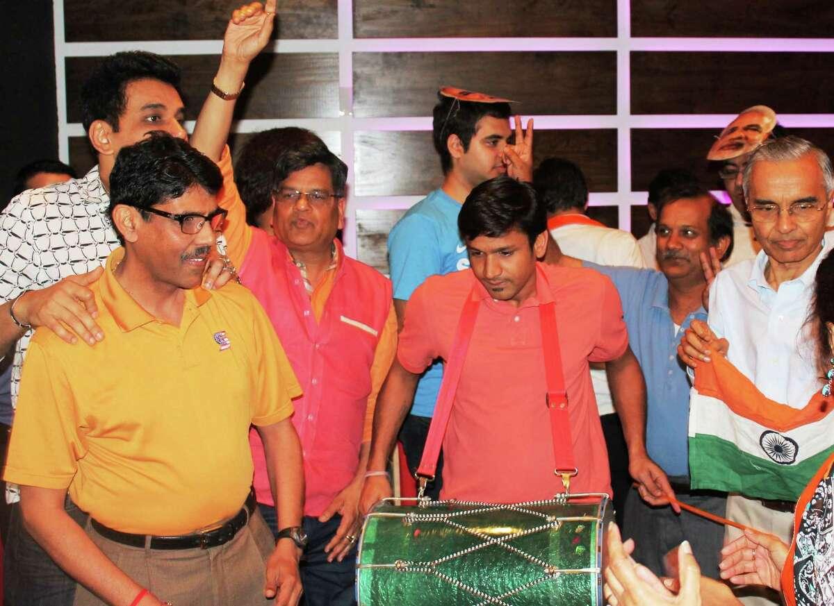 Sunil T, from left, Vijay Pallod, Jugal Malani, Anand Bhattad on drums, Ramesh Prasad and Ramesh Bhutada celebrate the election of India's Narendra Modi at Bhojan Restaurant on Friday in Houston.