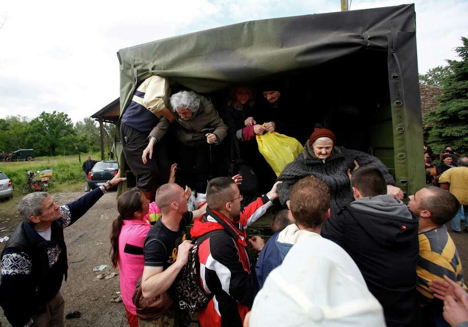 People help old women out of a military truck during evacuation from Obrenovac, some 30 kilometers (18 miles) southwest of Belgrade Serbia, Saturday, May 17, 2014. Record flooding in the Balkans leaves at least 20 people dead in Serbia and Bosnia and is forcing tens of thousands to flee their homes. Meteorologists say the flooding is the worst since records began 120 years ago. (AP Photo/Darko Vojinovic) ORG XMIT: XDMV127 Photo: Darko Vojinovic / AP