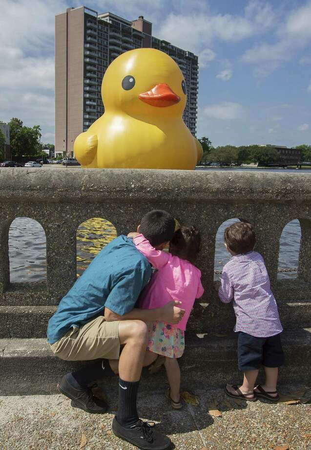 "Alonzo Lapitan,15, with his sister and brother, Aniston and Anderson, both 2, of Virginia Beach get a look at the 40- foot ""Rubber Duck"" in the Hague inlet by artist Florentijn Hofman  at the Chrysler Museum of Art in Norfolk, Va, on Saturday, May 17, 2014. Photo: Bill Tiernan, Associated Press / The Virginian-Pilot"