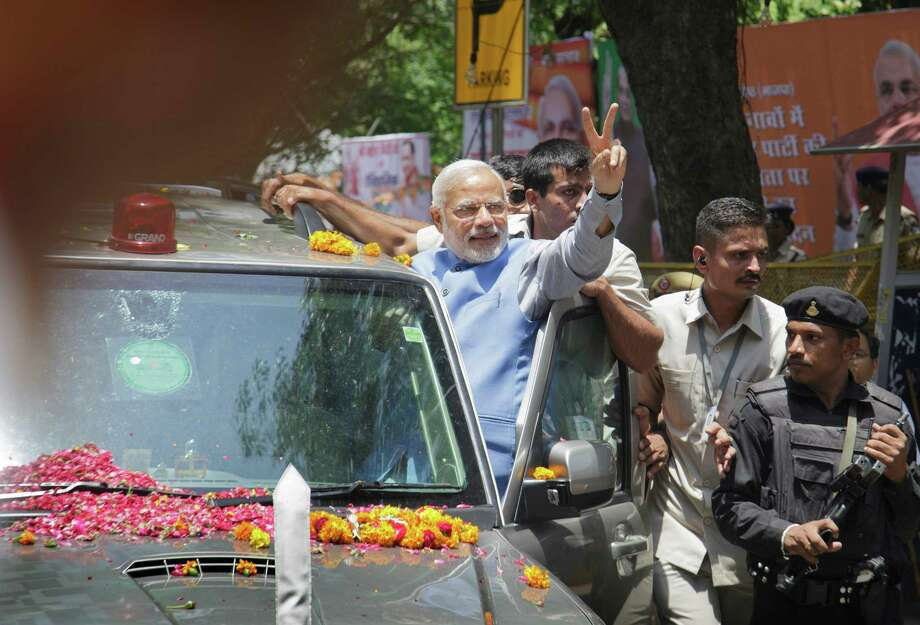 Narendra Modi emerges from his vehicle Saturday  to acknowledge the cheers as he enters New Delhi. Photo: KUNI TAKAHASHI, STR / NYTNS