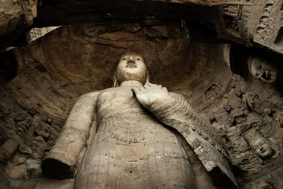 A nearly 50-foot high Buddha dating to around the sixth century in the Yungang Grottoes is endangered by pollution. Photo: GILLES SABRIE, STR / NYTNS