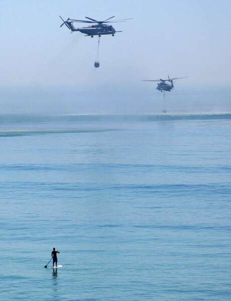 A paddle boarder watches as two firefighting helicopters scoop water from the Pacific Ocean off of San Clemente, Calif., to help quell blazes Friday. Photo: Bailey Bianco, HONS / Bailey Bianco
