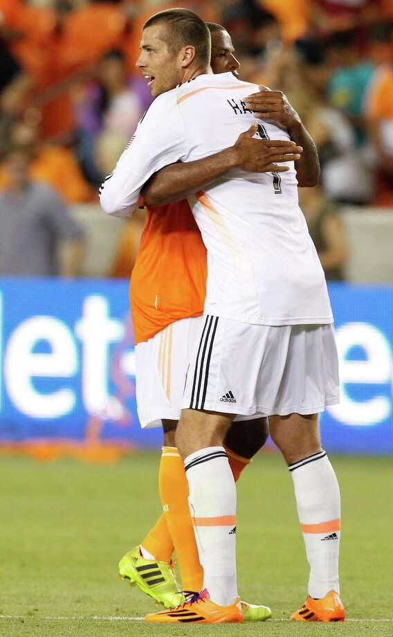 Houston Dynamo defender Jermaine Taylor (4) hugs Houston Dynamo goalkeeper Tally Hall (1) after they defeated the Los Angeles Galaxy on May 17, 2014 at BBVA Compass Stadium in Houston, Texas. Dynamos won 1 to 0. Photo: Thomas B. Shea, For The Chronicle / © 2014 Thomas B. Shea
