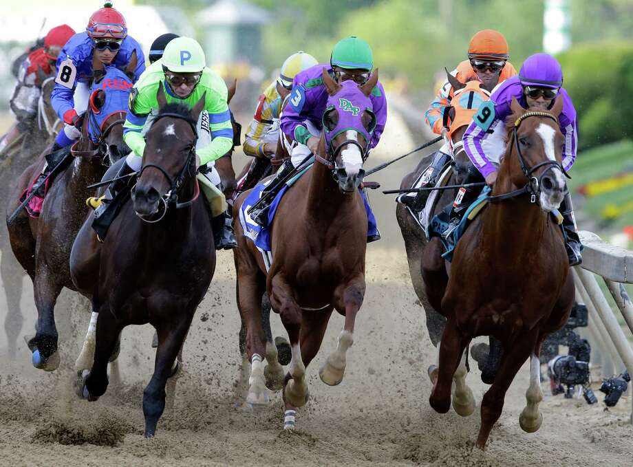 California Chrome, center, ridden by Victor Espinoza, looks for a way to break free of the pack as the field clears the first turn Saturday. Photo: Patrick Semansky, STF / AP