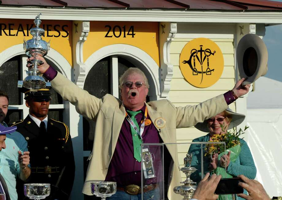 Owner Steven Coburn, center holds the winner's trophy aloft after California Chrome won the second leg of thoroughbred racing's Triple Crown with his win in the 139th running of The Preakness Stakes Saturday evening May 17, 2014 at Pimlico Race Course in Baltimore, Maryland.      (Skip Dickstein / Times Union) Photo: SKIP DICKSTEIN