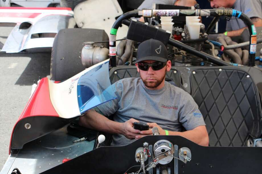 Mechanic Jimmy Gadberry sitting in a McLaren M6B owned by Toluca Lake Classic Motorsports