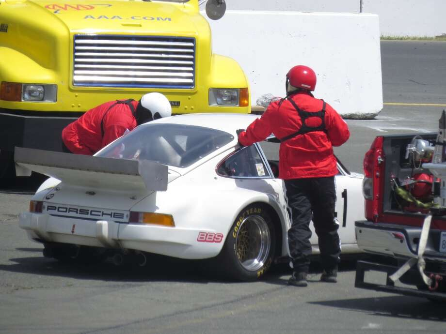 Track emergency workers checking out a Porsche that had pulled into an area off the track.