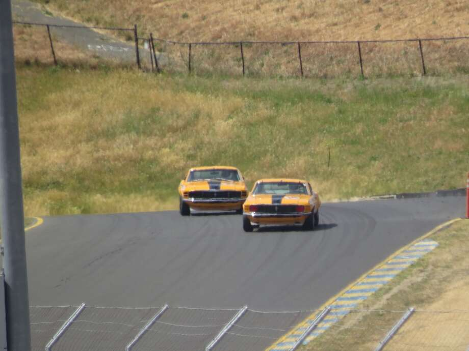 Two Ford Mustangs crest a hill on the 2.52-mile course.