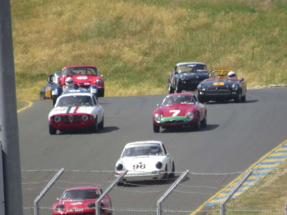 A bunch of cars grouped close together shortly after the start.