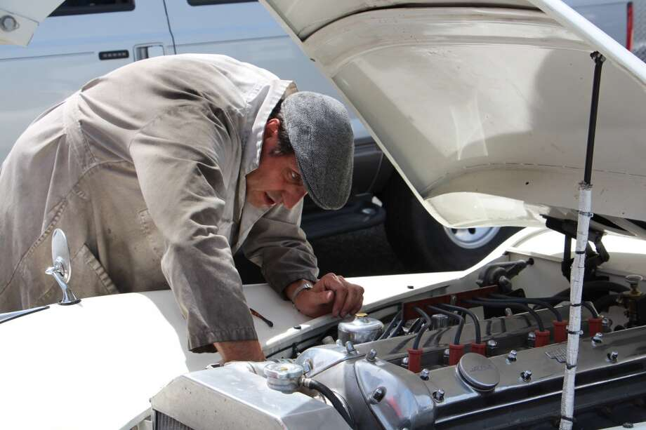 "James Alder working on a 1952 Jaguar XK-120, which, he said, ""is broken at the moment."""