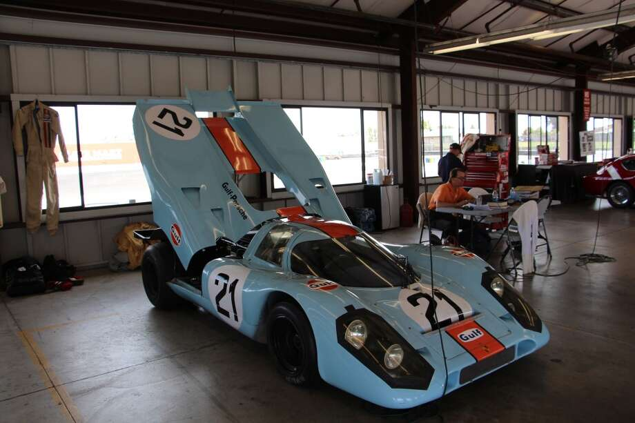 A 1970 Gulf-Wyer Porsche 917 owned and driven by Chris MacAllister (at table, right) of Indianapolis, Ind. MacAllister said the car was campaigned mainly by Pedro Rodriguez and ran at Le Mans, Spa-Francorchamps, Watkins Glen and Brands  Hatch, among other circuits.
