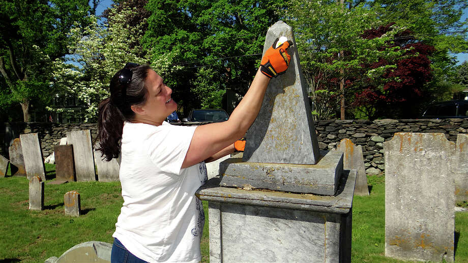 Carol St. John scrubs lectin off a grave marker during a cleanup project at the historic Greenfield Hill Cemetery on Saturday morning. Photo: Mike Lauterborn / Fairfield Citizen