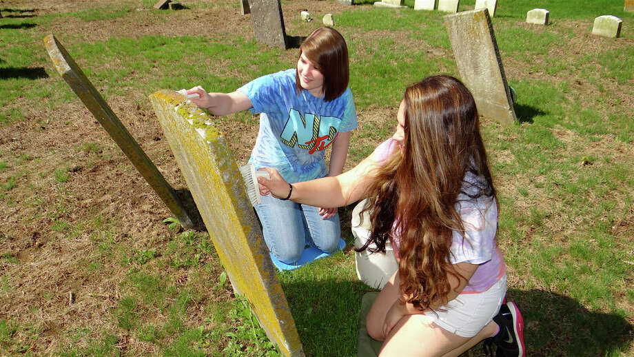 Kelly Logan and Marcella Manoni collaborate to clean a historic headtsone Saturday at the Greenfield Hill Cemetery. Photo: Mike Lauterborn / Fairfield Citizen