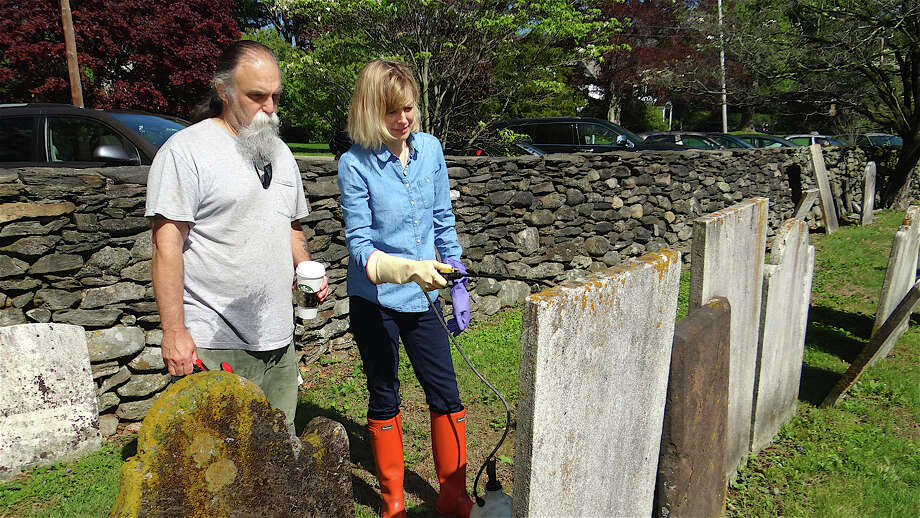 Wayne Lyon guides Sandy Altieri in the cleaning process for historic grave markers at the Greenfield Hill Cemetery. Photo: Mike Lauterborn / Fairfield Citizen