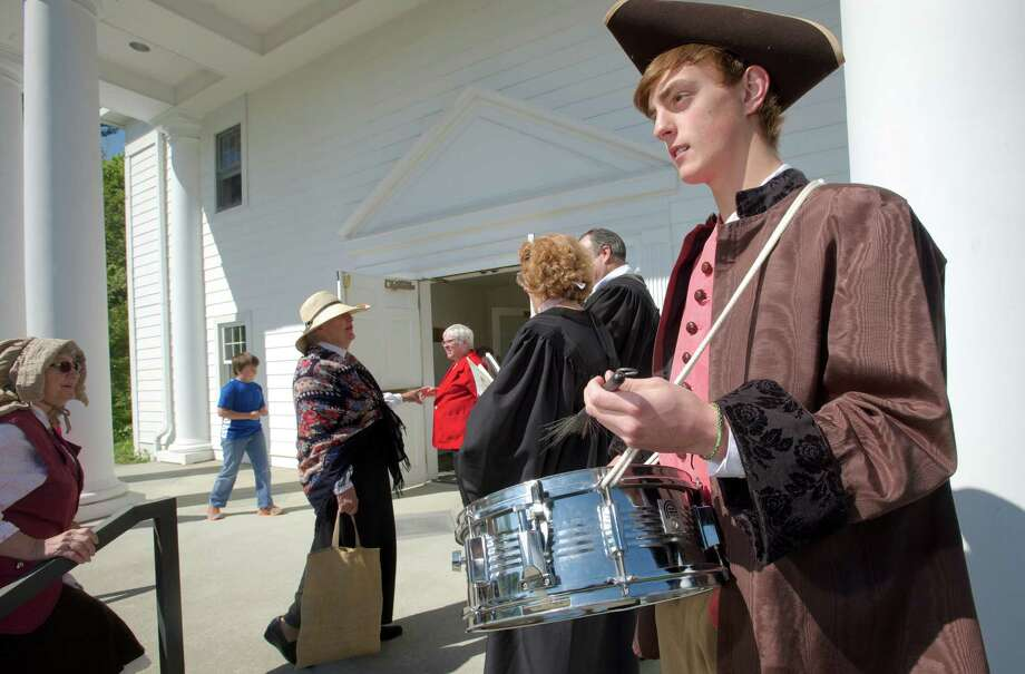 Shay DeMarche, 17, of  Newtown, drums the congregation to worship in front of the Newtown Congregational Church, on West Street, on Sunday, May 18, 2014. The church is celebrating its 300th anniversary and members dressed in colonial costumes and walked from their original meeting house, now the Newtown Meeting House, located at the flagpole in Newtown, Conn, to their present sanctuary, on West Street. The original meeting house did not have a bell so a drummer was used to summon people to worship. Photo: H John Voorhees III / The News-Times Freelance